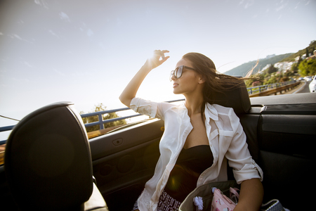 Photo pour View at young attractive woman drive in cabriolet at seaside - image libre de droit