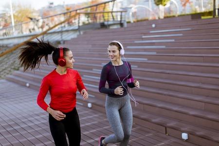 Photo pour Two pretty young women running in urban area - image libre de droit