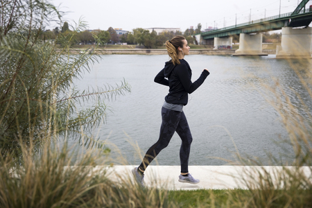 Photo pour Young woman running by the river - image libre de droit