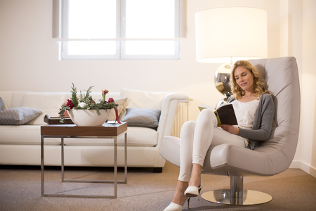 Photo pour Young woman at home sitting on modern chair  in the room and reading book - image libre de droit