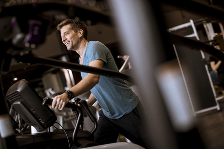 Foto per Young man doing exercise on elliptical cross trainer in sport fitness gym club - Immagine Royalty Free