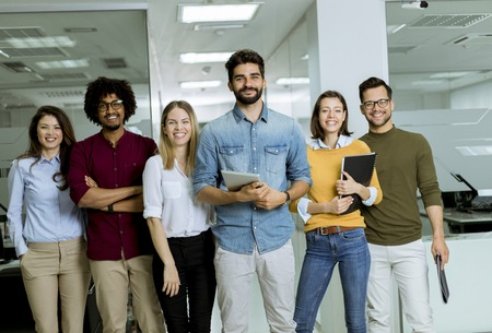 Photo for Portrait of young successful creative business team looking at camera and smiling in the office - Royalty Free Image
