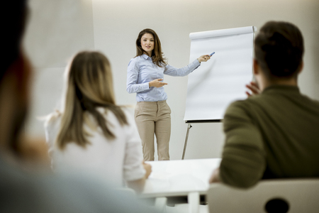 Photo for Creative positive female leader talking about business plan with students during workshop in the small office - Royalty Free Image