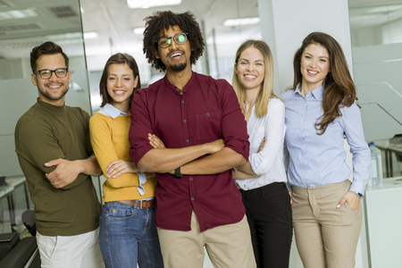 Photo for Portrait of group of young excited business people standing in office - Royalty Free Image