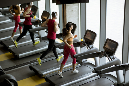 Foto per Man and woman doing cardio workout on treadmills in fitness club - Immagine Royalty Free