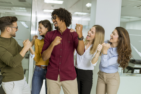 Photo for Portrait of group of young excited business people with hands up standing in office - Royalty Free Image