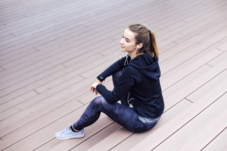 Photo pour Beautiful girl relaxing after a long run in the city and listening music - image libre de droit