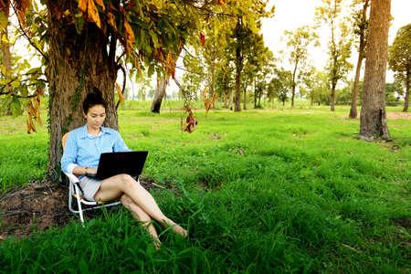 Foto de Business woman using laptop in the field - Imagen libre de derechos