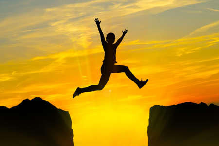 Foto de Silhouette of young person jumping over the mountains at sunset - Imagen libre de derechos
