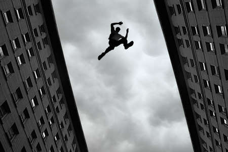 Photo pour Man jumping over building roof against gray sky background - image libre de droit