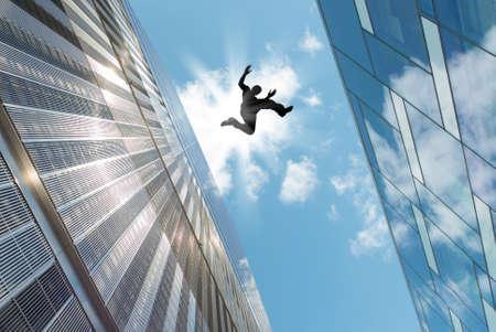 Foto de Man jumping over building roof against blue sky background - Imagen libre de derechos