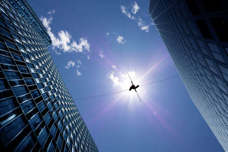 Photo pour Highline walker in blue sky between two buildings concept of risk taking and challenge - image libre de droit