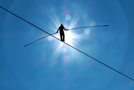 Foto de Tightrope walker balancing on the rope concept of risk taking and challenge - Imagen libre de derechos