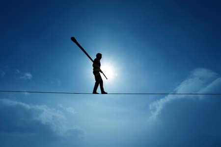 Foto de Tightrope walker balancing on the rope concept of risk taking and challenge - Imagen libre de derechos