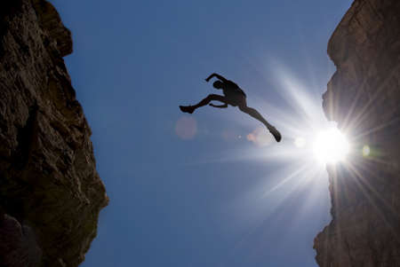 Photo pour Man jumping over precipice between two mountains - image libre de droit