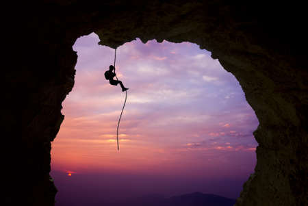 Foto de Man rock climber silhouette over bright sunset - Imagen libre de derechos