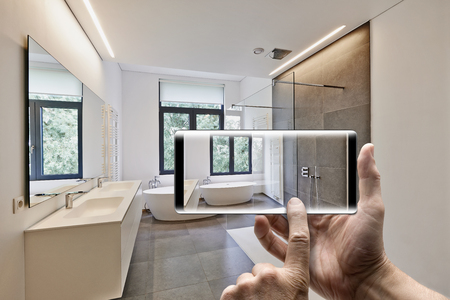 Foto de Mobile device with man hands taking picture in  tiled bathroom with windows towards garden - Imagen libre de derechos