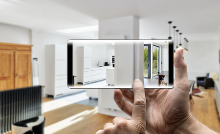 Foto de Two hands holding a mobile Smartphone and take a picture in a Modern luxury living room and kitchen - Imagen libre de derechos