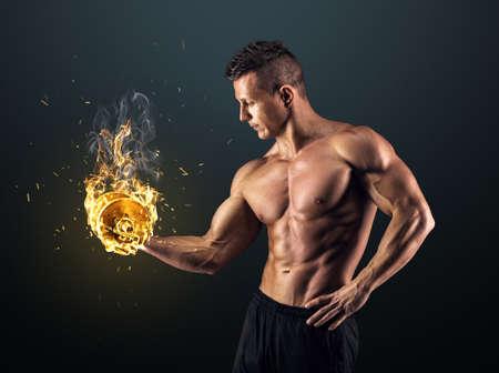 Foto de Handsome power athletic man bodybuilder doing exercises with dumbbell. Fitness muscular body on dark background. - Imagen libre de derechos