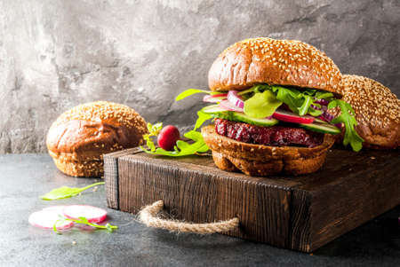 Foto de Healthy vegan burgers with beets, carrots, spinach, arugula, cucumber, radish and tomato sauce, whole grain buns on a rustic wooden board on a dark stone background, selective focus, copy space - Imagen libre de derechos
