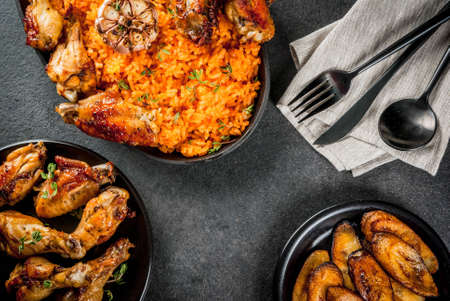 Foto de West African national cuisine. Jollof rice with grilled chicken wings and fried bananas plantains.On gray stone table. Copy space  top  view - Imagen libre de derechos