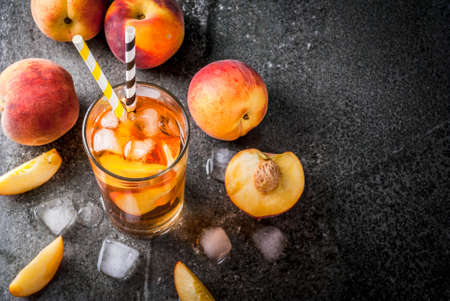 Photo pour Summer refreshment drinks. Iced tea with pieces of organic home-made peach of nectarine. On a black stone background, with ice and ingredients. Copy space top view - image libre de droit