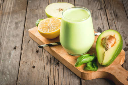 Photo for Healthy food. Dietary breakfast or snack. Green smoothies from yoghurt, avocado, banana, apple, spinach and lemon. On a rustic wooden table, with ingredients. Copy space - Royalty Free Image