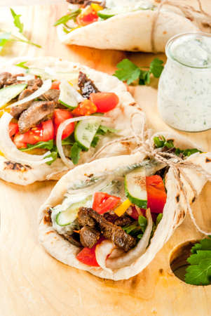 Photo pour Healthy snack, lunch. Traditional Greek wrapped sandwich gyros - tortillas, bread pita with a filling of vegetables, beef meet and sauce tzatziki. - image libre de droit