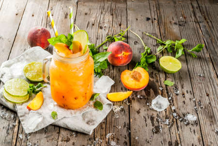 Photo for Summer drinks, cocktails. Vegan food. Peach smoothies, juice or lemonade. In a mason jar, with lime, chopped ice and mint leaves. On an old rustic wooden table with ingredients. Copy space - Royalty Free Image