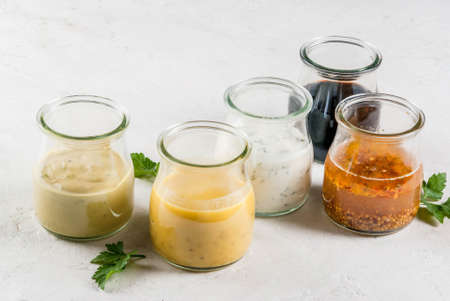 Photo pour Set of dressings for salad: sauce vinaigrette, mustard, mayonnaise or ranch, balsamic or soy, basil with yogurt. Dark white concrete table. Copy space top view - image libre de droit