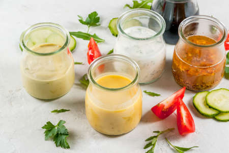 Photo pour Set of dressings for salad: sauce vinaigrette, mustard, mayonnaise or ranch, balsamic or soy, basil with yogurt. Dark white concrete table, with greenery, vegetables for salad. Copy space - image libre de droit