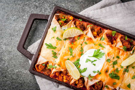 Photo for Mexican food. Cuisine of South America. Traditional dish of spicy beef enchiladas with corn, beans, tomato. On a baking tray, on a black stone background. Top view copy space - Royalty Free Image
