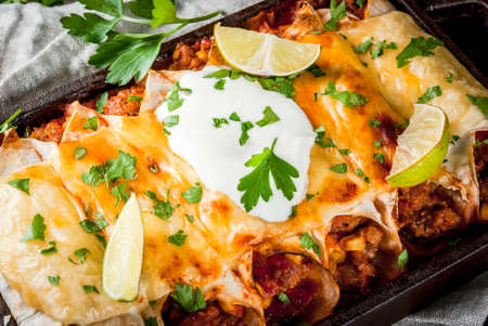 Photo for Mexican food. Cuisine of South America. Traditional dish of spicy beef enchiladas with corn, beans, tomato. On a baking tray, on old rustic wooden background. Close view - Royalty Free Image
