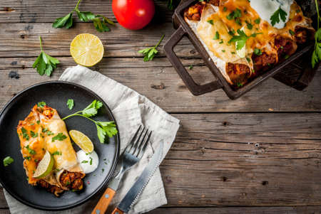 Photo for Mexican food. Cuisine of South America. Traditional dish of spicy beef enchiladas with corn, beans, tomato. On a baking tray, on old rustic wooden background. Copy space top view - Royalty Free Image