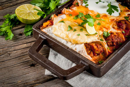 Photo pour Mexican food. Cuisine of South America. Traditional dish of spicy beef enchiladas with corn, beans, tomato. On a baking tray, on old rustic wooden background. Copy space - image libre de droit