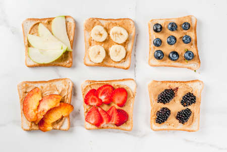 Foto de Traditional American and European summer breakfast: sandwiches of toast with peanut butter, berry, fruit apple, peach, blueberry, blueberry, strawberry, banana. White marble table. copy space top view - Imagen libre de derechos