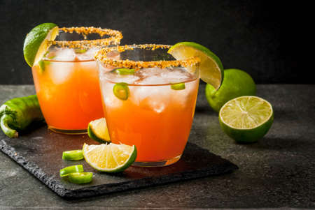Foto de Alcohol. Traditional Mexican South American cocktail. Spicy michelada with hot jalapeno peppers and lime. On a dark stone table. Copy space - Imagen libre de derechos