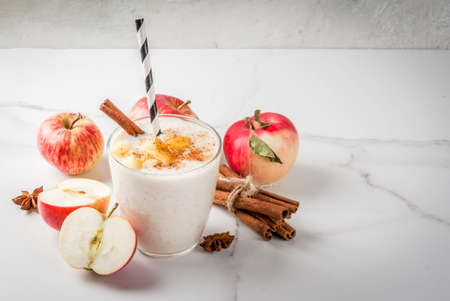 Photo for Healthy vegan food. Dietary breakfast or snack. Apple pie smoothies, with apples, yogurt, cinnamon, spices, walnuts. In a glass, on a white marble table. Copy space - Royalty Free Image