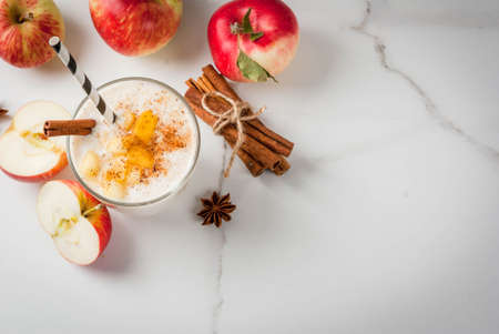 Photo for Healthy vegan food. Dietary breakfast or snack. Apple pie smoothies, with apples, yogurt, cinnamon, spices, walnuts. In a glass, on a white marble table. Copy space top view - Royalty Free Image