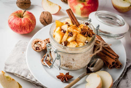 Foto de Healthy vegan food. Dietary breakfast or snack. Apple pie overnight oats, with apples, yogurt, cinnamon, spices, walnuts. In a glass, on a white marble table. Copy space - Imagen libre de derechos
