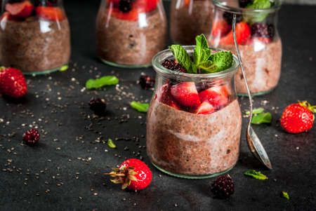 Foto de Healthy vegan breakfast. Dessert. Alternative food. Pudding with chia seeds, fresh strawberries, blackberries and mint. On a dark stone background. Copy space - Imagen libre de derechos