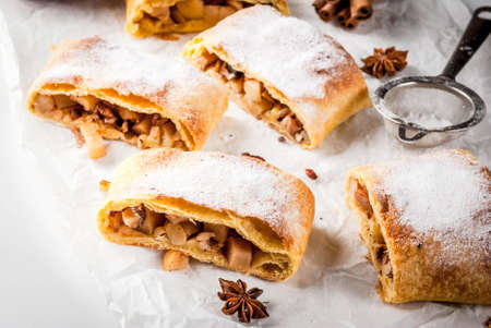 Foto de Home autumn, summer baking, puff pastries. Apple strudel with nuts, raisins, cinnamon and powdered sugar. On white marble table. Sliced, with ingredients. Copy space - Imagen libre de derechos