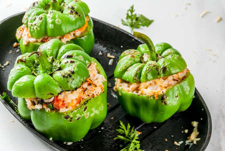 Photo for Autumn recipes. Homemade stuffed bell pepper with minced meat, carrots, tomatoes, herbs, cheese. On white marble table, in baking pan, Copy space - Royalty Free Image