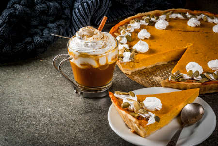 Foto de Traditional autumn dishes. Halloween, Thanksgiving. Spicy pumpkin pie with whipped cream & pumpkin seeds, pumpkin latte with cinnamon on black stone table with blanket. Copy space - Imagen libre de derechos