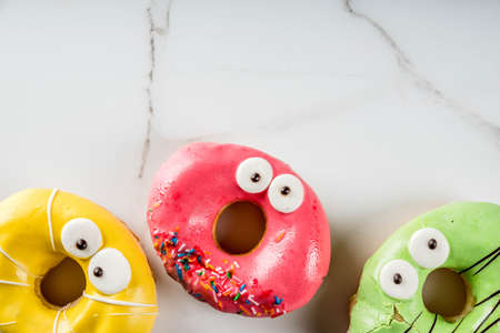 Photo for Ideas for children treats on Halloween. Colorful  donuts in the form of monsters with eyes, green, yellow, red chocolate sugar icing. On a white marble table. Copy space top view - Royalty Free Image