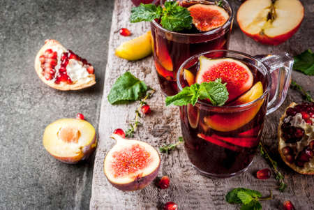 Photo for Warming autumn, winter cocktail drinks recipes. Hot red fruit sangria with apples, plums, figs, pomegranate, mint, cinnamon, thyme, lemon. On dark stone table, with wooden cutting board, copy space - Royalty Free Image