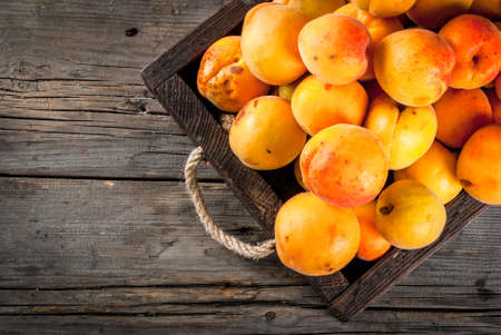 Photo for Summer fruits. Fresh raw organic farm apricots in a wooden box, a tray, on an old wooden rustic table. Copy space top view - Royalty Free Image