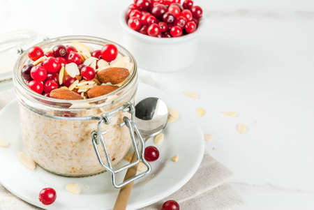Foto de Recipe for a healthy winter breakfast, ideas for Christmas morning. Overnight oatmeal with almonds, cranberries, sugar. On a white marble table. copy space - Imagen libre de derechos