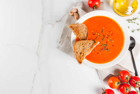 Photo for Tomato cream soup with olive oil and herbs, with toasted bread, on white marble background, copy space top view - Royalty Free Image