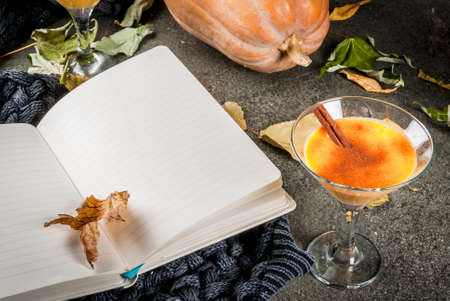 Photo for Fall and winter drinks. Thanksgiving and Halloween cocktails. Pumpkin pie margarita with cinnamon stick, on black stone table. Cozy home, with autumn leaves, plaid, pumpkin, book, copy space - Royalty Free Image